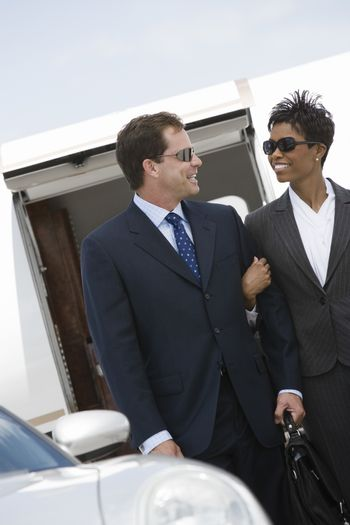 Multiethnic business couple standing together with airplane in the background at airfield