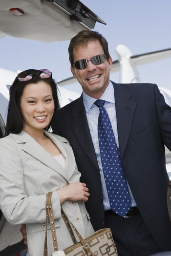 Portrait of business couple standing with airplane in the background at airfield