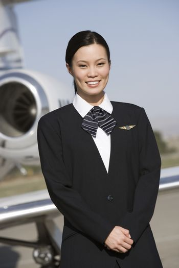 Portrait of a pretty stewardess standing with airplane in the background at airfield