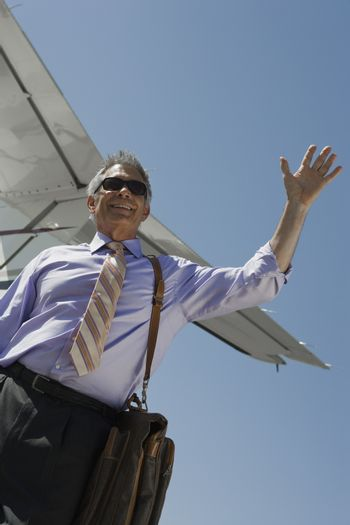 Low angle view of senior businessman waving hand against airplane tail at airfield