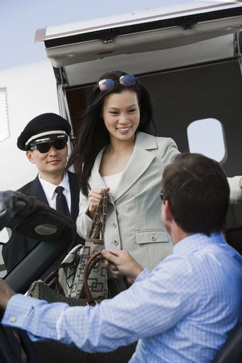 Business man receiving Korean businesswoman with airplane captain in the background at airfield