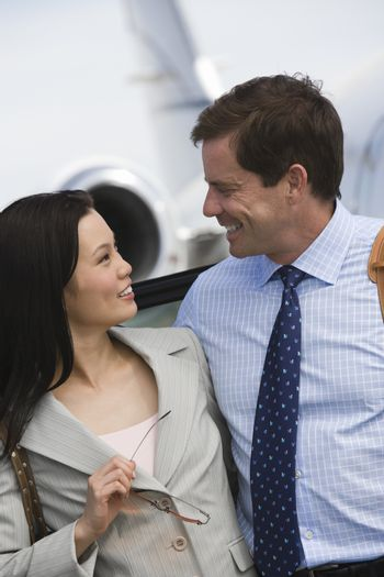 Happy business couple looking each other at airfield