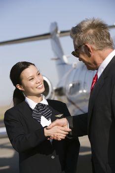 Senior business man thanking pretty Korean stewardess at airfield