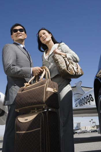 Low angle view of business couple standing together at airfield
