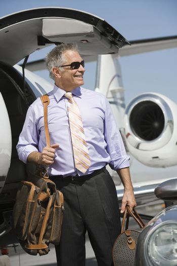 Senior happy businessman standing by airplane with luggage at airfield