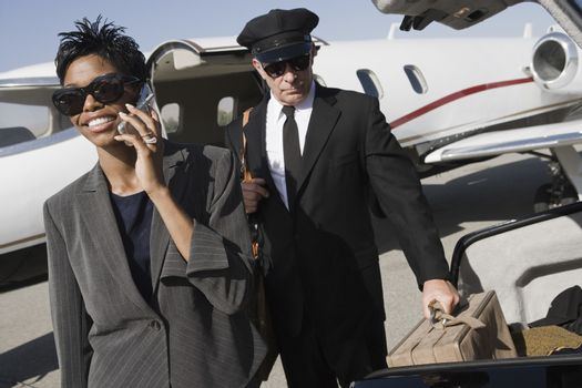 Business woman on a call while driver keeping luggage in car at airfield