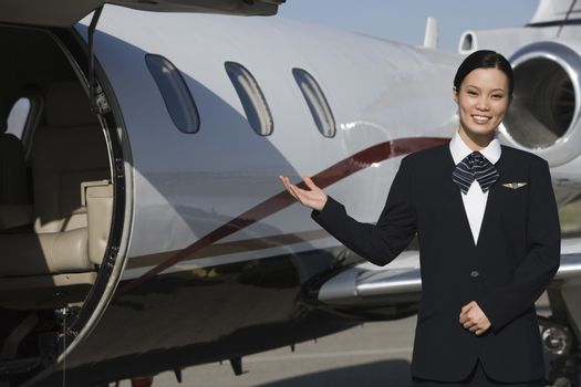 Portrait of a beautiful stewardess gesturing by airplane at airfield