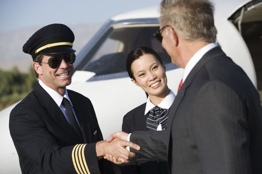 Senior businessman shaking hands with an airplane captain and stewardess in the background at airfield