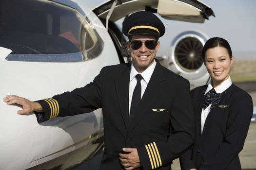 Two happy cabin crew members standing together by an airplane at airfield
