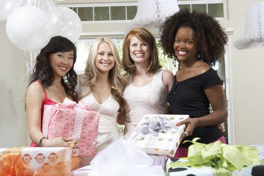 Portrait of bride and friends holding gifts at hen party