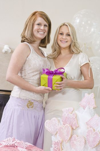 Bride And Her Friend Holding Gift Box At Hen Party