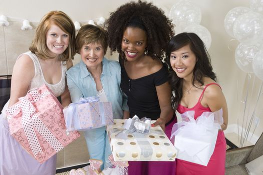 Portrait of happy women holding gifts at hen party