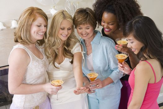 Bride standing together with friends watching her engagement ring