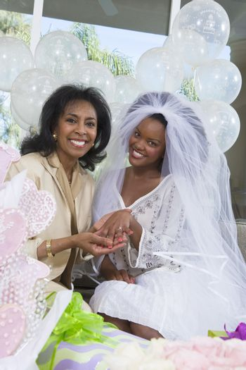 Bride with mother showing her engagement ring at hen party