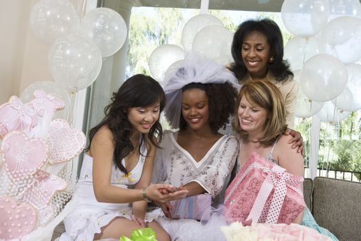 Happy bride showing engagement ring to friends at hen party