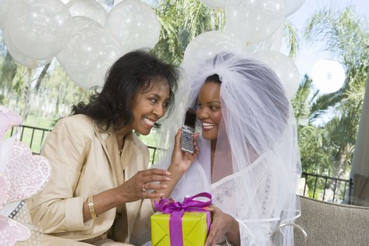 Bride using mobile phone with mother at hen party
