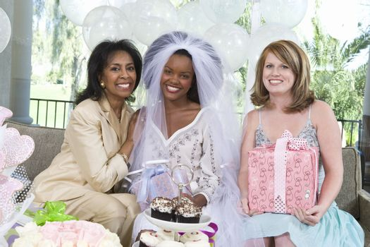 Portrait of bride sitting with her mother and friend at hen party