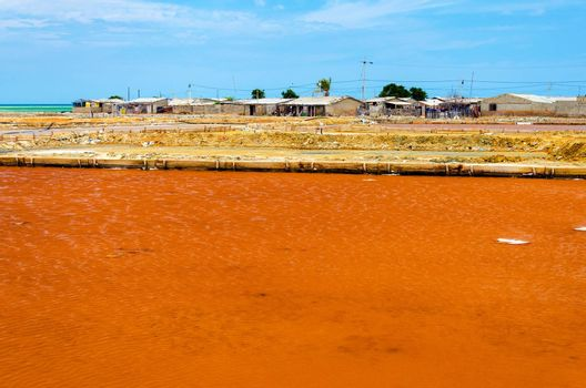 Red salt pool by a slum in Manaura, Colombia