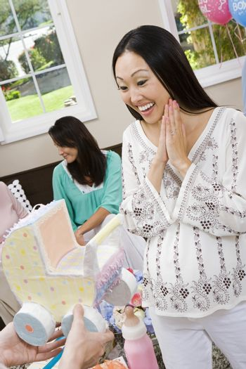 Surprised pregnant woman receiving baby carriage at a baby shower