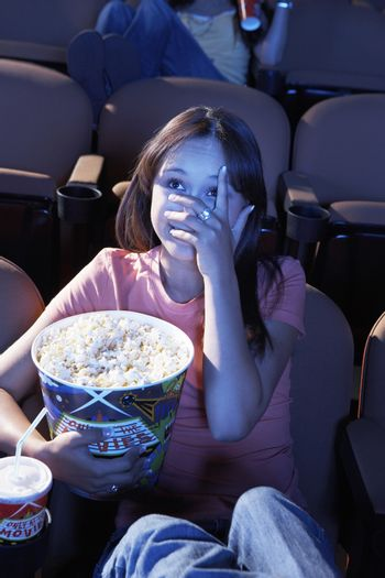 Young female hiding her face while watching horror shot in a movie
