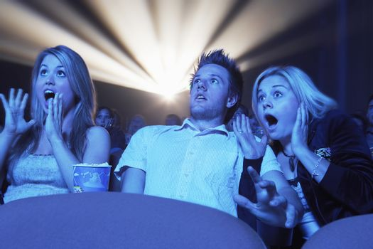 Young people screaming while watching horror movie in the theatre