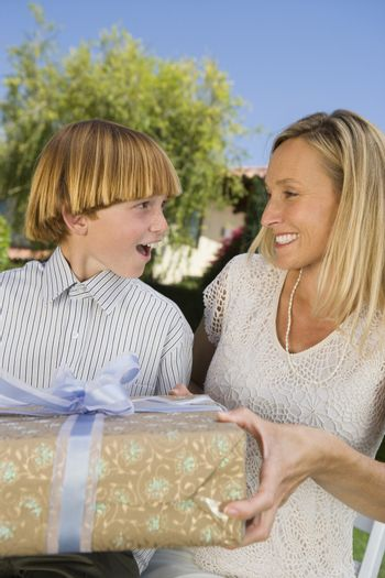 Happy mother gifting her son a present on birthday