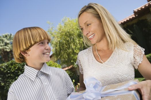 Happy mother giving gift to son at birthday