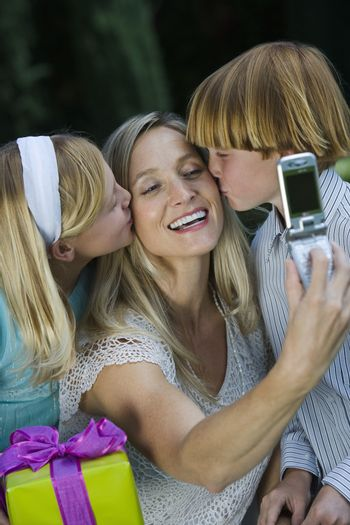 Happy mother clicking self photo while kids kissing her on cheeks