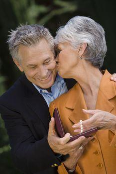 Senior wife kissing husband on cheek for the gift