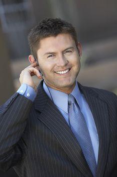 Happy businessman with earphone looking away