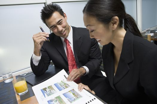 An Asian businessman showing property samples to his business partner