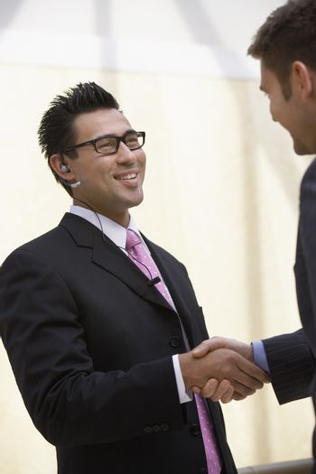 Happy businesspeople shaking hands with each other at office