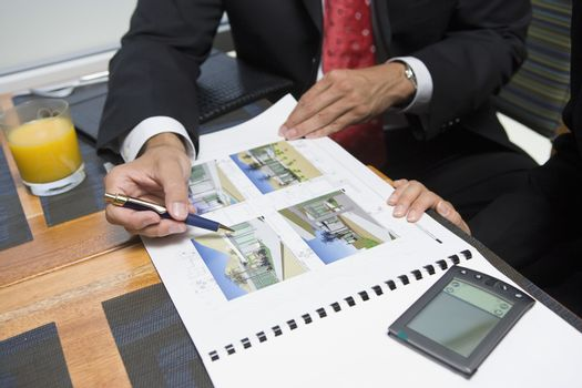 Mid section of businessman showing property samples to his business partner