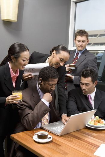 Five business people using laptop in office meeting