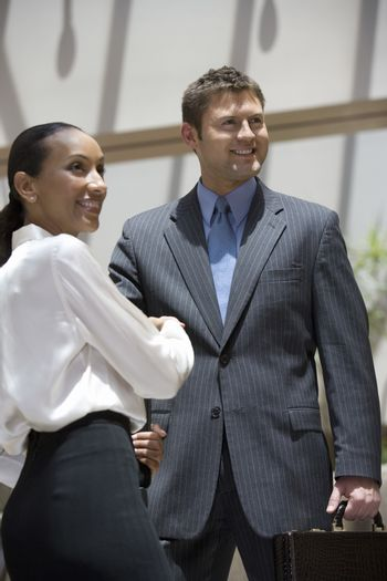 Happy businessman and woman looking away