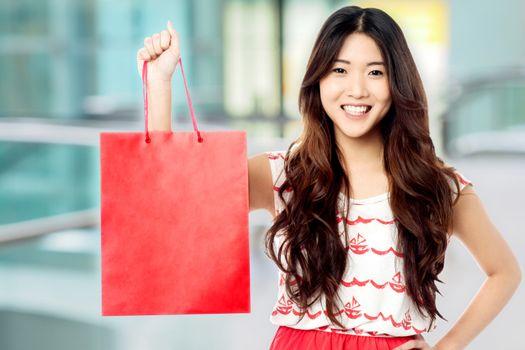 Pretty shopaholic girl with shopping bag