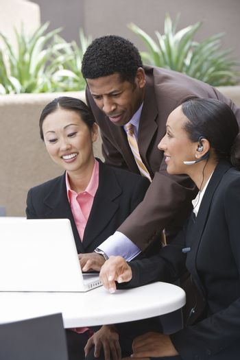 Multi ethnic business people in a meeting with a laptop