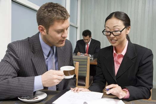An Asian businesswoman explaining contraction to her business partner with man in the background at restaurant