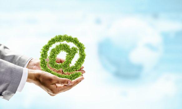 Image of human hand holding plant shaped like at symbol