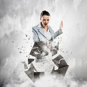 Image of businesswoman crashing recycle stone symbol