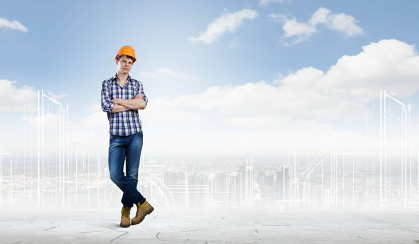 Image of man builder with arms crossed on chest against urban scene