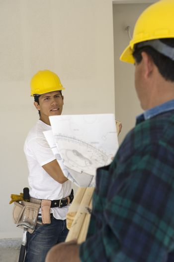 Two construction workers with blueprint at workplace