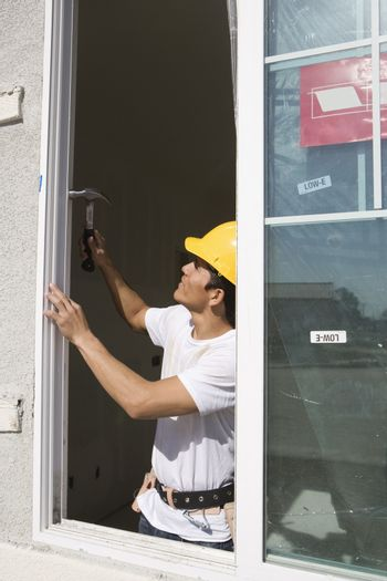 Male architect installing new window at construction site