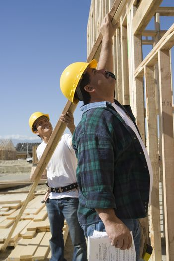 Supervisor helping coworker at construction site