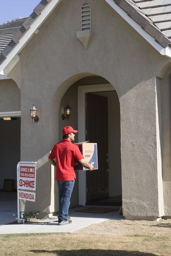 Worker delivering cardboard box into new house