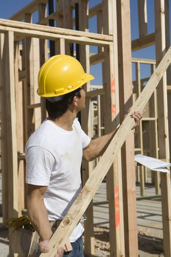 Construction worker in hardhat holding up plank at site
