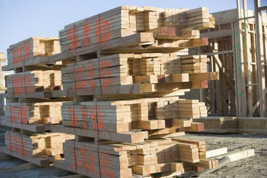 Stacked of wooden planks at construction site