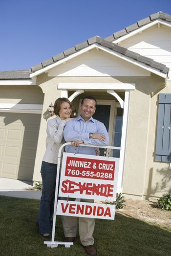 Happy mature couple outside home with sold sign