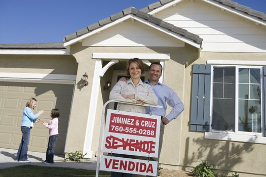 Happy mature parents with daughters outside home with sold sign