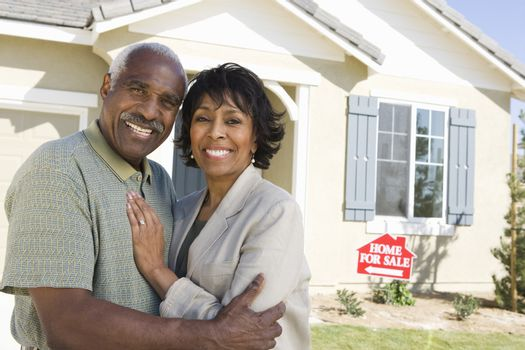 Portrait of happy African American couple in front of home for sale